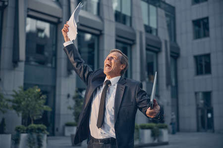 Cheerful excited man in suit holding notebook and papers while screaming with joy and raising hands