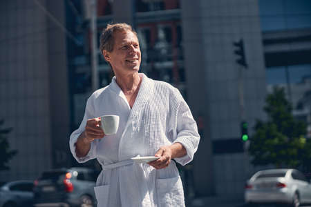 Cheerful gentleman in white bathrobe holding cup of coffee and smiling while spending time outdoors