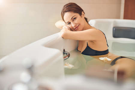 Lovely young Caucasian woman in a bikini taking a soothing bath in a wellness center Archivio Fotografico