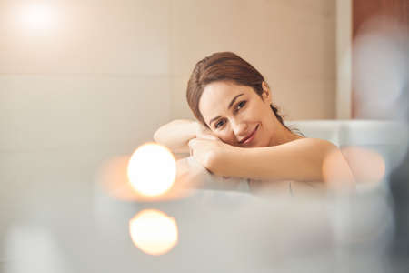 Portrait of a smiling beautiful young woman relaxing in a bath in a spa center