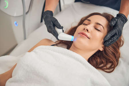 Female resting with closed eyes while getting procedure at beauty salon with help of cavitation device