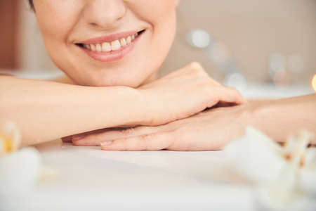 Cropped photo of Caucasian lady with the perfect skin smiling while relaxing alone