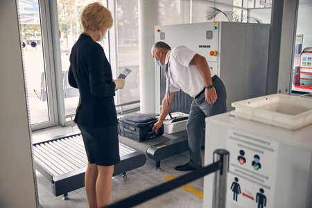 Male airport worker in medical mask putting travel suitcase on baggage conveyor belt while lady holding airplane ticket