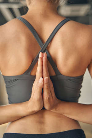Close up of young woman joining hands behind her back while doing yoga exercise Imagens