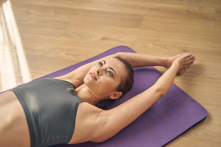 Attractive lady lying on fitness mat and joining raised hands above her head while practicing yoga in studio Banque d'images