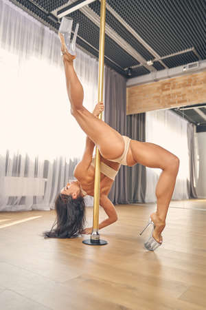 Sexy young woman in lingerie demonstrating perfect pole dance skills Banque d'images