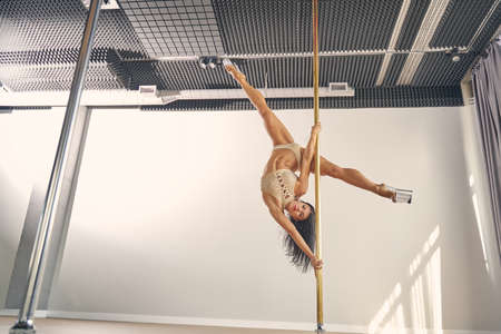 Attractive female dancer in elegant underwear demonstrating pole dance tricks