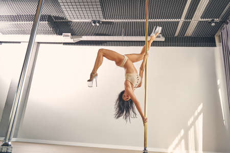 Attractive young woman with perfect body dancing on pylon in studio