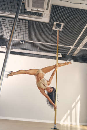 Beautiful young woman with perfect body dancing on pylon in studio