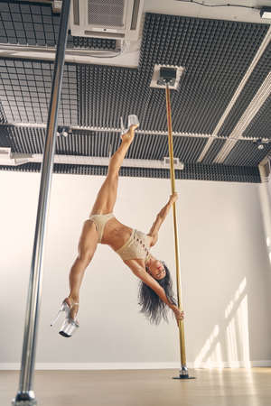 Attractive female dancer with perfect body performing pole dance tricks Banque d'images