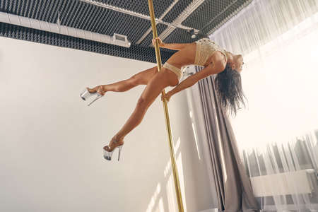 Beautiful female dancer wearing underwear and high heels while dancing on pylon in studio Banque d'images