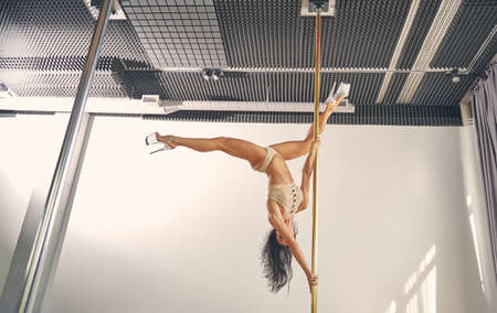 Sexy female dancer wearing lingerie and high heels while doing pole dance tricks