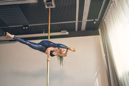 Attractive female dancer in latex leggings performing pole dance tricks