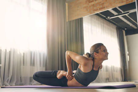 Beautiful sporty lady looking away and smiling while doing yoga exercise