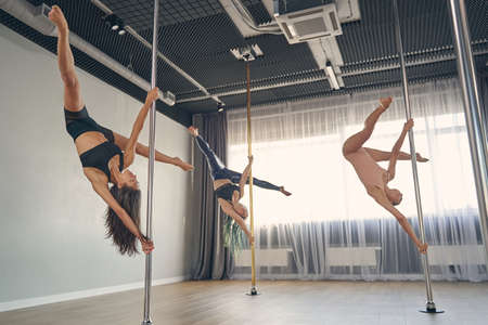 Charming female dancers in gymnastics clothes doing acrobatic tricks while dancing on pylons in studio