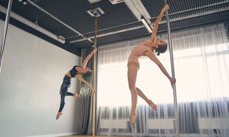Attractive female dancers in gymnastics clothes showing acrobatic performance on pylons in studio