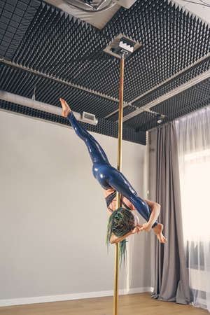 Beautiful female dancer in latex leggings showing acrobatic performance on pylon
