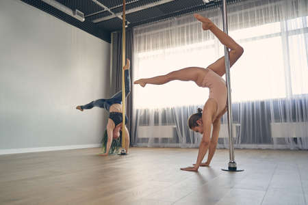 Two beautiful female dancers in gymnastics clothes performing pole dance tricks