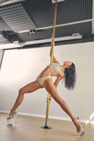 Attractive female dancer wearing elegant underwear and high heels while doing pole dance moves in studio