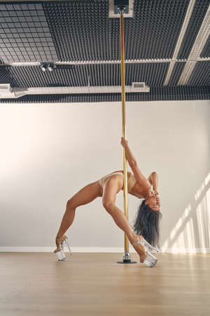 Attractive female dancer wearing elegant underwear and high heels while demonstrating pole dance skills in studio