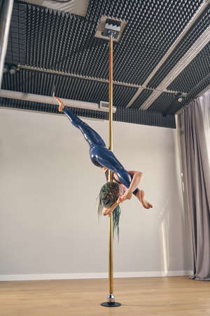 Charming female dancer in latex leggings doing upside down split while showing acrobatic performance on pylon Banque d'images
