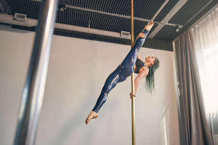 Beautiful young woman in latex leggings doing acrobatic exercise in pole dance studio Banque d'images