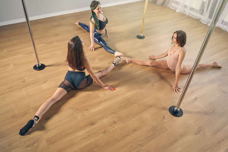 Three beautiful female dancers doing the splits while training together at dance class