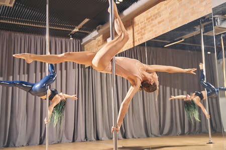 Skillful female dancers in gymnastics clothes showing acrobatic performance on pylons in pole dance studio