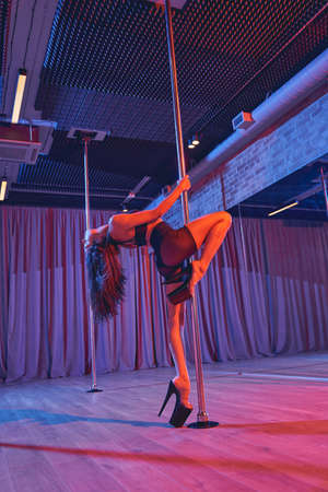 Sexy female dancer in black shorts performing pole dance tricks Banque d'images