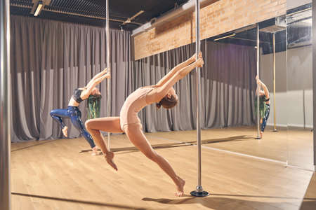Two beautiful young women in gymnastics clothes showing acrobatic performance in pole dance studio