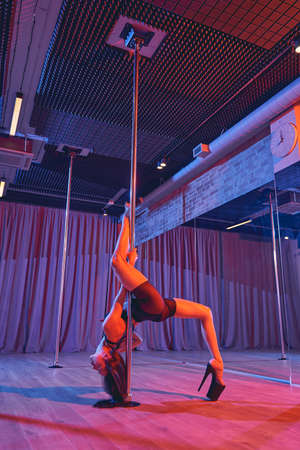 Sexy young woman wearing high heels while dancing on pylon in studio with dim neon lighting Banque d'images