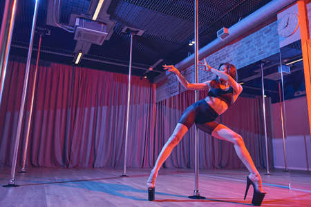 Attractive young woman wearing sexy high heels while dancing on pylon in pole dance studio