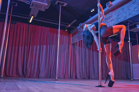 Beautiful female dancer wearing high heels and black shorts while dancing on pylon in studio with dim neon lighting