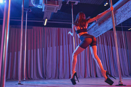 Attractive young woman wearing black shorts and high heels while dancing on pylon in club with neon lighting