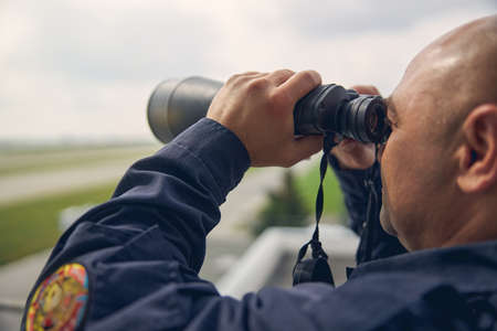 Back view portrait of handsome man while looking into the distance through the binoculars