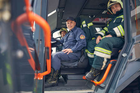 Portrait of happy cheerful driver of big truck with firefighters near him Banco de Imagens