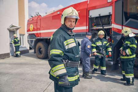 Close up portrait of man in yellow helmet standing at the outdoors in front of team firefighters