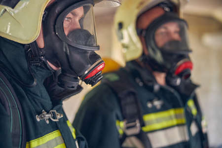 Close up portrait of firefighters in green fireproof uniform listening his commander while standing in the indoors