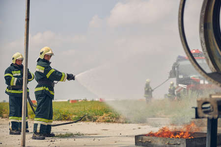 Side view of two firemen in the protective uniform and yellow helmets splashing water from hose
