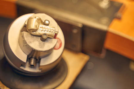 Top view of a metal pendant gripped in an engraving block ball vise on the workbench