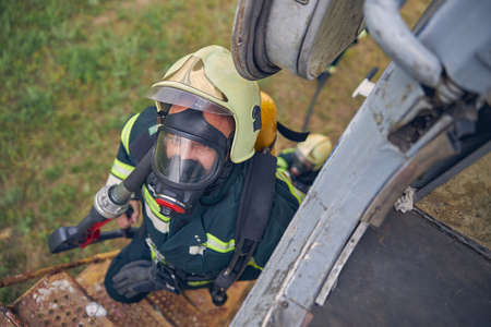 Top view portrait of firefighter in safe helmet going up on stairs with full equipment