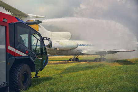 Close up portrait of fire truck while fire machine spray water on the big white plane in the outdoors