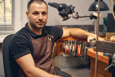 Waist-up portrait of an attractive male worker in a jeweler apron sitting in a workshop