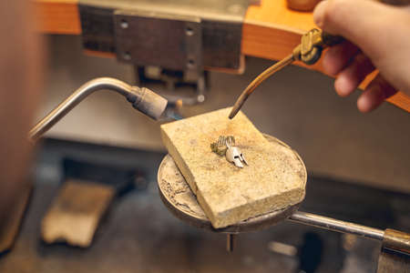 Cropped photo of a male worker using a pair of tools for repairing a piece of jewelry Imagens