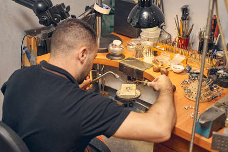 Back view of a skilled young dark-haired craftsman working on a metal piece of jewelry