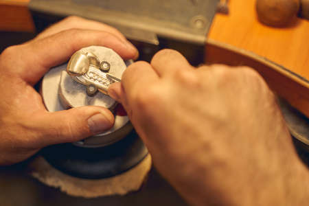 Close up of Caucasian male hands treating a metal pendant in an engraving block ball vise