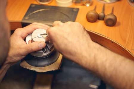 Cropped photo of a professional male jeweler cutting out a design on a piece of metal