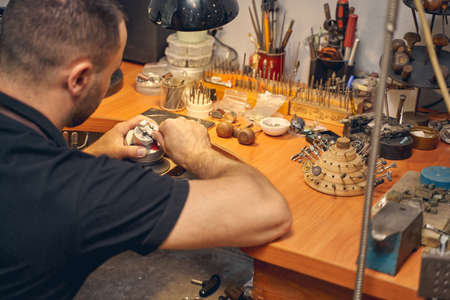 Back view of a young Caucasian man treating a piece of jewelry at his workbench