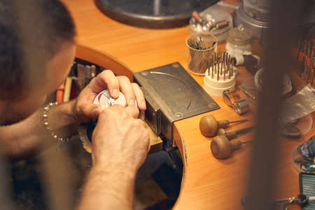 Cropped photo of a dark-haired Caucasian male jeweler making a copper pendant in his workshop Imagens