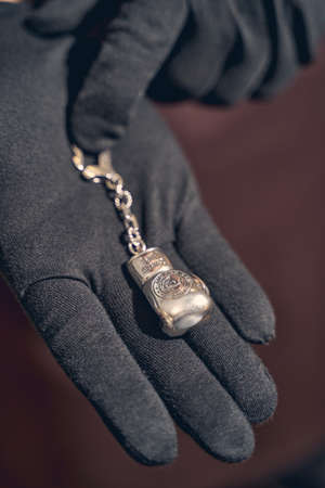 Cropped photo of a craftsperson holding a boxing glove keychain in front of the camera